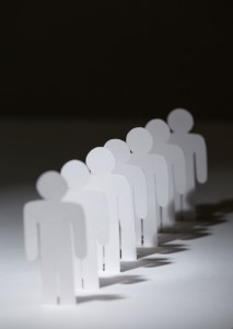 Close up of group of papermen standing in a row. Lots of copies of one paper man on black background